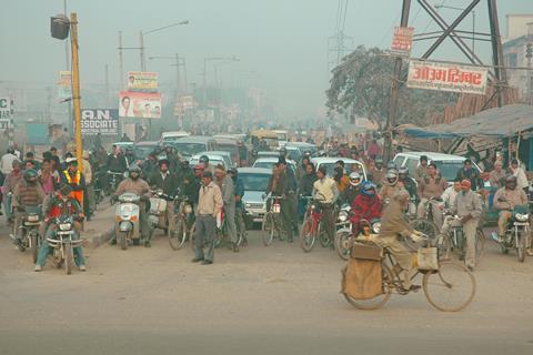 New Delhi rush hour, vehicles and pedestrians at a crossroad