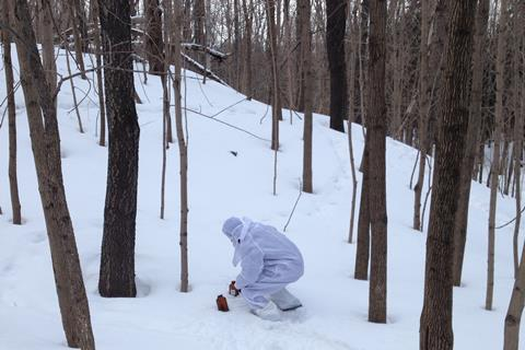 A person in a white hazmat suit collecting snow samples in a forest