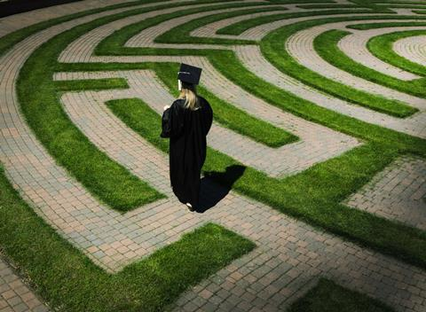 A person wearing academic clothes walking through a maze