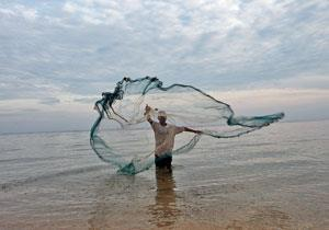 A fisherman in Baucau, East Timor, casts a net in the water to catch small fish