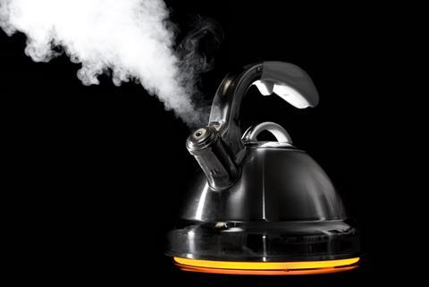 Black background, old-fashioned style kettle emitting vapour