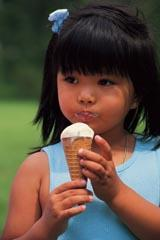 A child eating a vanilla ice cream