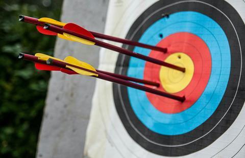 Four arrows embedded in an archery target