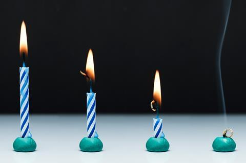 An image showing four stripey blue and white candles, all alight, from left to right, they show the progression of burning