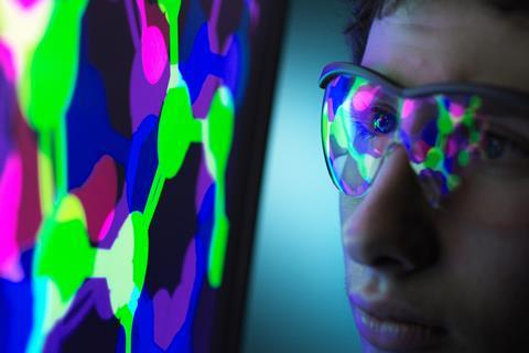 An image showing a student who is sat very close to a computer screen; a molecular structure is on the display, which reflects on his safety spectacles