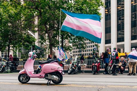 A pink moped and person carry a trans pride flag on a San Francisco street