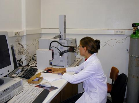 An image showing a woman in a lab coat seated at a desk using a gas chromatography olfactometer