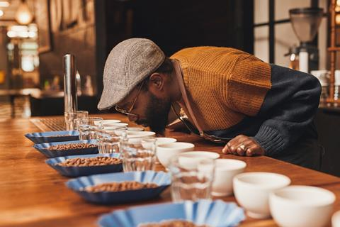 An image showing a man wearing a flat cap and glasses behind a table covered with bowls of different kinds of coffee beans, glasses and cups. He's testing the quality of the coffee beans by smelling them.