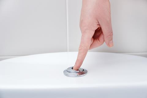 An image showing a woman's forefinger pressing the toilet flush button