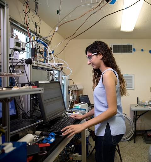 Catherine Masoud operates a chemical ionization mass spectrometer in one of the test house's adjacent trailers
