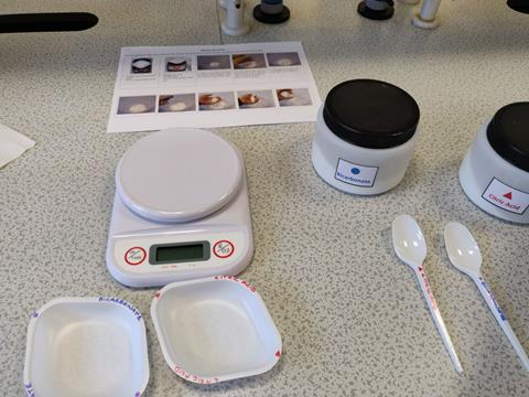 A photo of equipment and step-by-step instructions on a workbench for a practical chemistry experiment; the dishes, labels and containers are colour coded