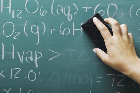 An image showing the hand of a teacher erasing chemical formulae from a blackboard