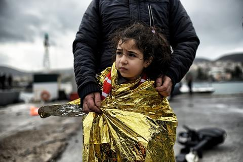 An image showing a young migrant girl wrapped in a thermal blanket