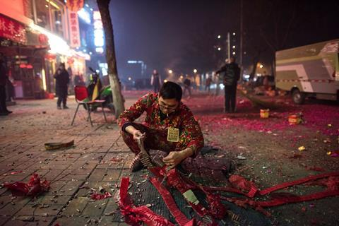 An image showing a waiter from a restaurant lighting fireworks on a street in Beijing on February 7, 2016, the eve of the Lunar New Year.