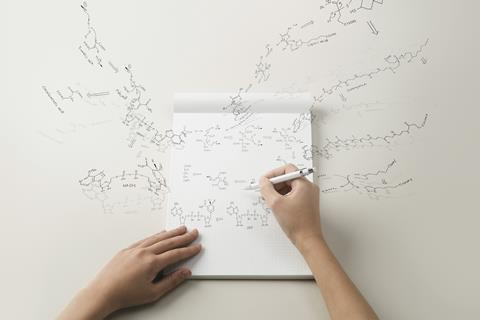 An image showing the hands of a student writing organic chemistry formulas on a white pad and spilling over onto the table