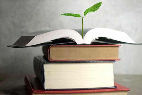 A plant sprouting from the pages of a book
