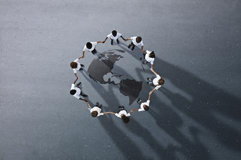 An image showing children holding hands gathered in a circle around a drawing of Planet Earth