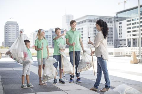 An image showing a group of volunteering children collecting garbage with litter sticks