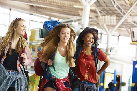 Three young women with backpacks in a departure lounge