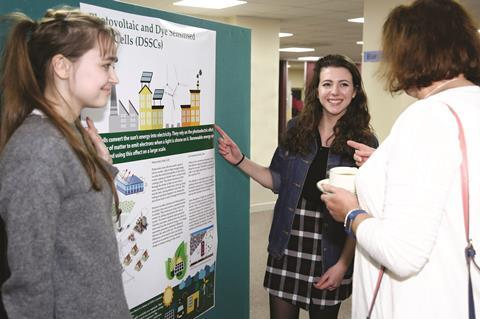 Three people gathered round a scientific poster