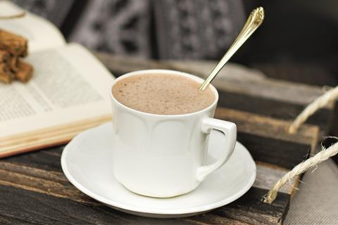 A spoon in a white mug of hot chocolate