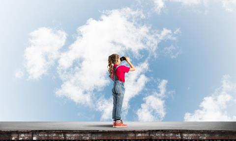 Girl looking into the sky with binoculars