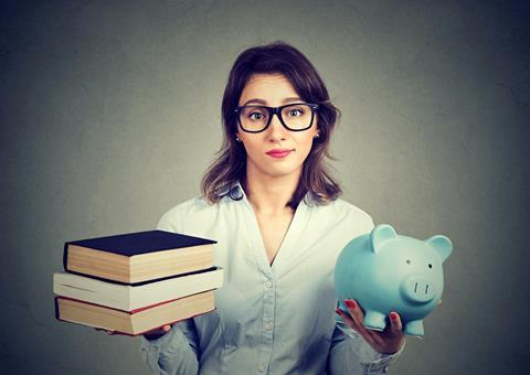 Young woman with glasses, books in one hand, piggy bank in other, pained expression