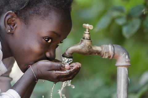 An African child drinking from a tap