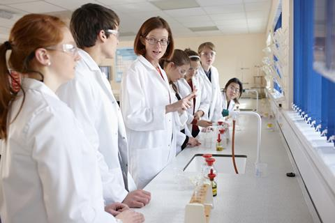 Teacher and several students along a bench in a chemistry lab
