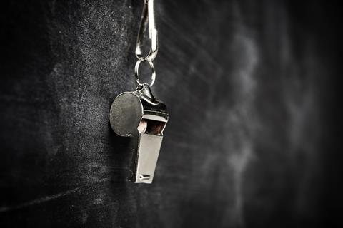 A picture of a silver whistle hanging on a blackboard