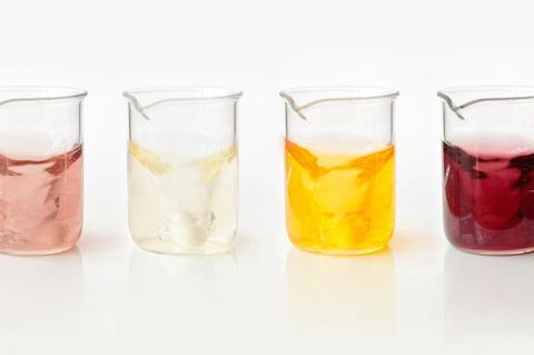 Series of four glass beakers, each containing a different coloured solution
