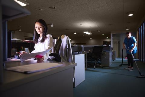 Woman working late at her desk, cleaner vacuuming in background
