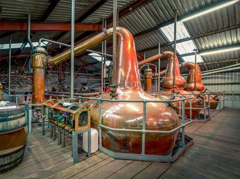 Whisky distillery in a warehouse, large brass stills