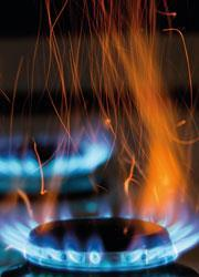 A gas hob showing a blue and orange flame