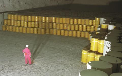 A person observing many yellow waste barrels