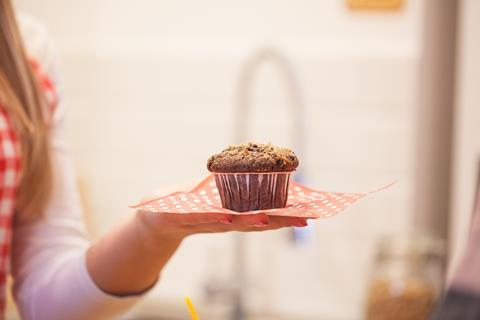 Cupcake on a red and white napkin on an outstretched hand