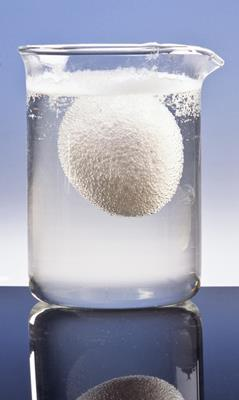 An egg in a glass beaker of vinegar